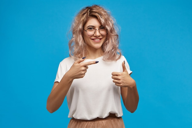 Kijk hier eens naar. horizontaal van prachtige charismatische jonge blanke vrouw met roze haar en lange zwarte nagels met duimen omhoog en wijsvinger, breed glimlachend