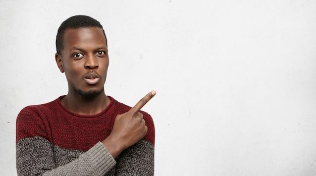 Kijk hier eens naar. verbijsterd en opgewonden jonge afro-amerikaanse man gekleed terloops wijzend zijn wijsvinger omhoog op lege grijze muur met copyspace