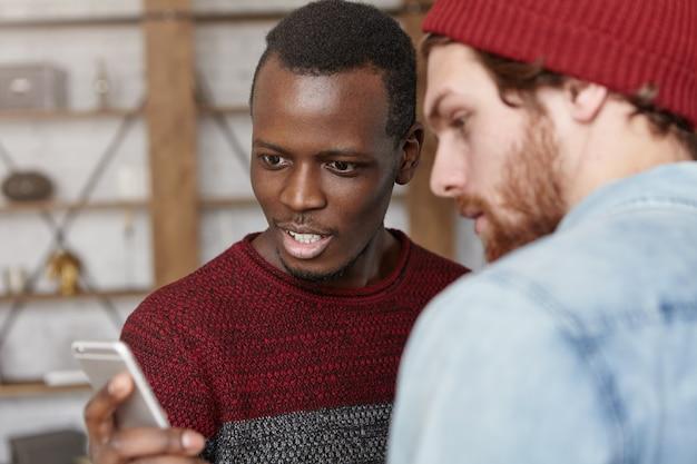 Kijk hier eens naar! verbijsterde en geschokte jonge zwarte man in casual trui met smartphone, die zijn blanke vriend zijn dromen op internet laat zien die hij nu tegen een veel lagere prijs kan kopen