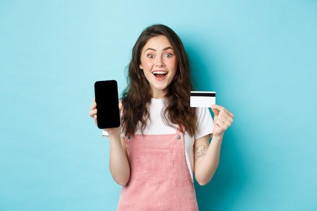 Kijk hier. opgewonden jong schattig meisje met leeg mobiel scherm en plastic creditcard, kijk verbaasd naar de camera, staande over blauwe achtergrond.
