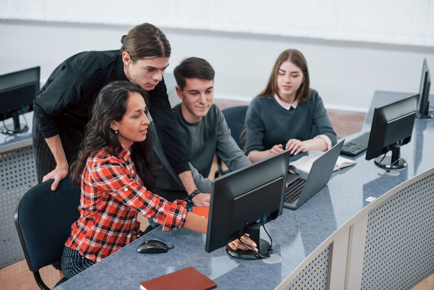 Kijk hiernaar. groep jonge mensen in vrijetijdskleding die in het moderne bureau werken