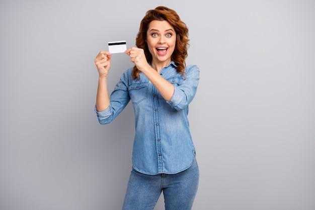 Kijk, ik krijg een gouden kaart! verbaasde gekke vrouw hold kredietbank onder de indruk van online debet betalingsdienst schreeuw wow omg draag stijl stijlvol trendy kleding geïsoleerde grijze kleur muur