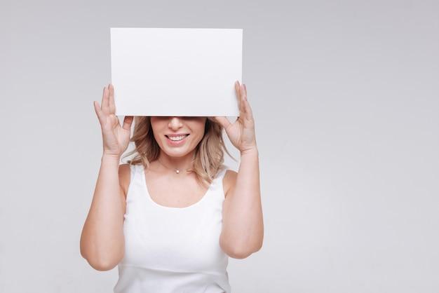 Kijk maar naar die glimlach. magnetische emotionele mooie vrouw die een vel papier vasthoudt en haar ogen verbergt tijdens het poseren