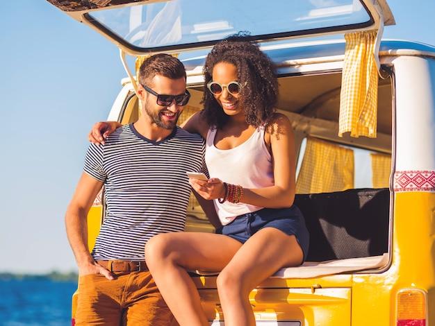 Kijk naar deze foto! vrolijk jong stel dat samen naar een mobiele telefoon kijkt terwijl ze allebei aan de kofferbak van een retro minibusje zitten met de zee op de achtergrond