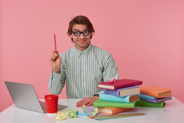 Kijk naar deze man, hij heeft een cool idee! benieuwd man met bril zit bij de tafel en werkt met laptop, kijkt naar de camera, houdt een potlood in de hand, geïsoleerd op roze achtergrond.