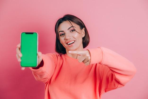 Kijk naar deze mobiele telefoon! blij blij vrouw wijst met wijsvinger naar leeg scherm, toont modern apparaat, blij verrast emoties.