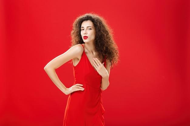 Kijk naar deze schoonheid. zelfverzekerde flirterige en sexy elegante vrouw met krullend haar in jurk die hand op heup houdt en sensueel ontroerende borst draait naar camera die lippen vouwt en iemand over rode muur verleidt.