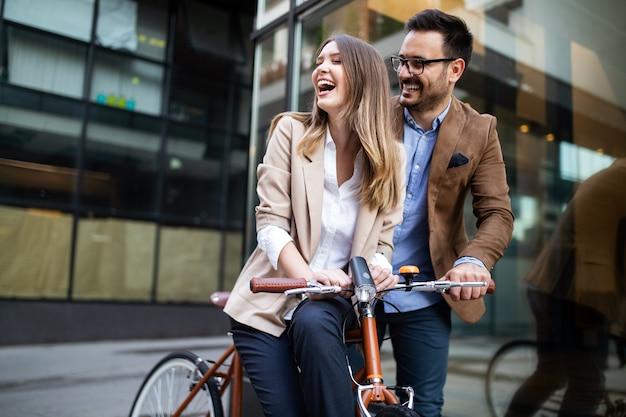 Kijk naar jonge gelukkige zakenmensen die buiten praten en glimlachen