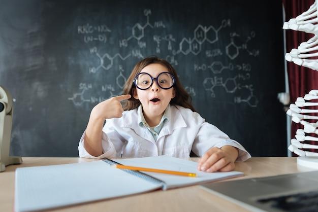 Kijk naar me. vrolijke positieve creatieve meisje zit in het laboratorium en huiswerk tijdens het maken van aantekeningen en het gebruik van laptop