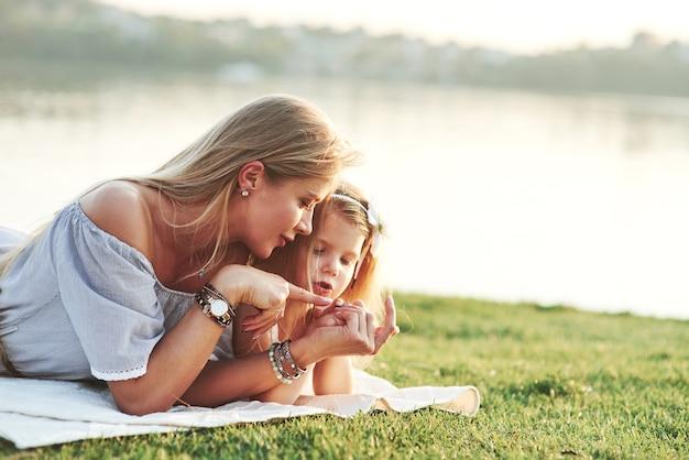 Kijk naar mijn vingernagels. foto van jonge moeder en haar dochter die goede tijd hebben op het groene gras met meer bij achtergrond.