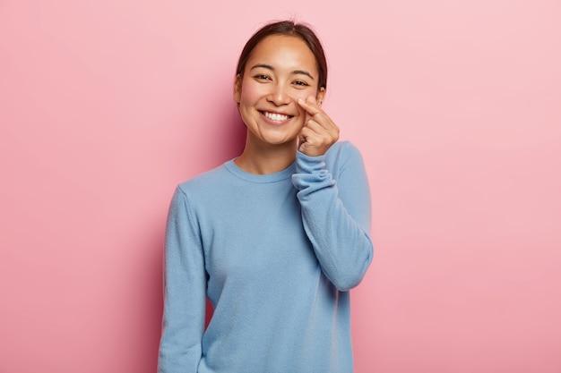 Kijk naar mijn wang. aangenaam uitziende aziatische vrouw raakt huid op gezicht, toont de frisheid en zachtheid, draagt geen make-up, donker gekamd haar, gekleed in een casual blauw sweatshirt, geïsoleerd op roze