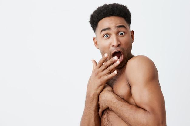 Kijk niet naar mij. close-up van een grappige man met een zwarte huid en een afrokapsel dat zich met handen sluit, toen een vriend in de badkamer kwam terwijl hij in bad was. lastige situaties