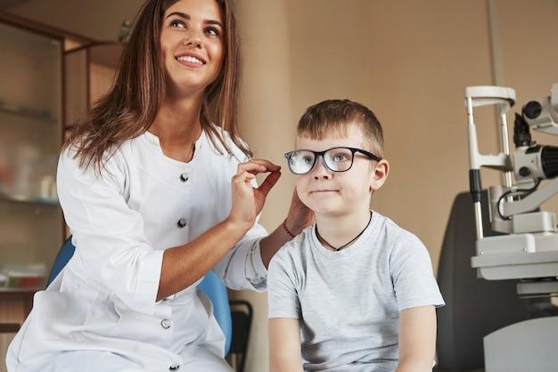Kijk nu naar dat bord met letters. kid zit in het kantoor van de dokter en probeert nieuwe blauwe glazen.