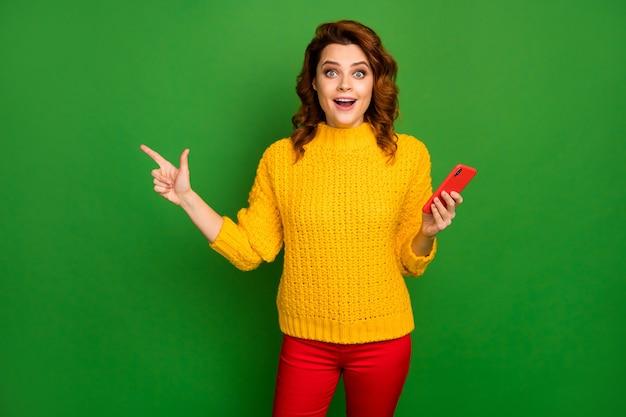 Kijk ongelooflijke advertenties! verrast vrouw wijs wijsvinger copyspace gebruik mobiele telefoon aanwezig sociaal netwerk promotie schreeuw slijtage gele trui broek geïsoleerd felle kleur muur
