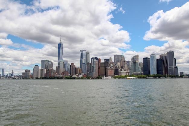 : kijk op de zeilboot die op de achtergrond door new yorkse havengebouwen van het eiland manhattan vaart.