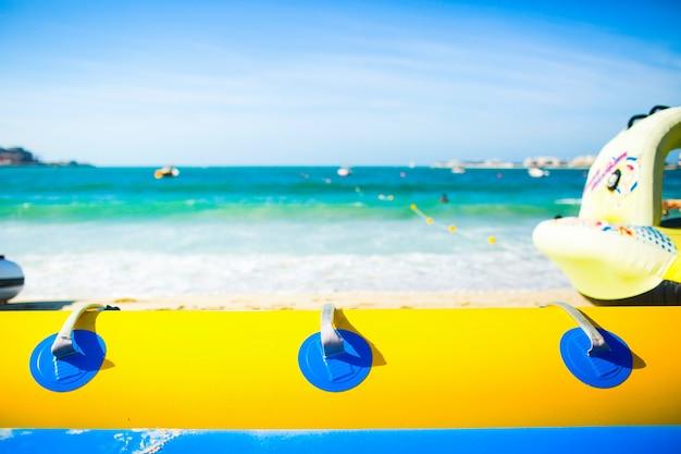 Kijk over blauwe en gele luchtbuis bij schuimende zeegolven onder zonnige lucht