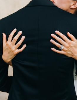 Kijk van achteren naar bruid knuffelen bruidegom tender. handen op zijn bac