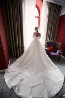 Kijk van achteren naar de bruid met de lange jurk die voor het raam staat