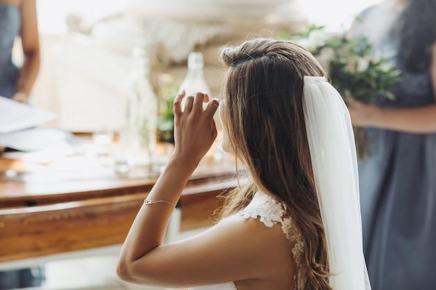 Kijk van achteren naar de charmante bruid die haar ogen aanraakt
