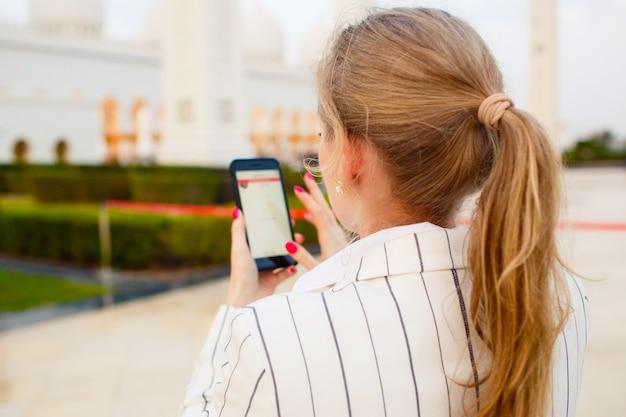 Kijk van achteren op blonde vrouw die met haar iphone werkt terwijl ze voor de grote moskee shekh zayed staat