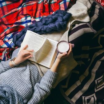 Kijk van bovenaf bij jonge dame koffie drinken terwijl ze een boek leest