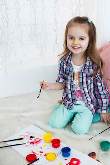 Kijk van bovenaf naar een charmant klein meisje met blauwe, rode en gele verven op de vloer