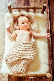 Kijk van bovenaf naar kleine baby op een houten bed met witte fu