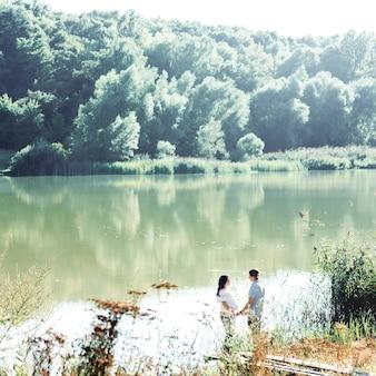 Kijk van veraf naar een mooi paar dat elkaars handen vasthoudt terwijl ze bij de rivier staan