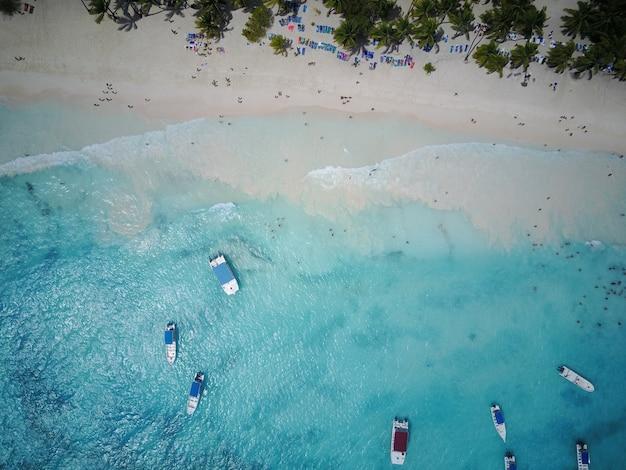 Kijk vanaf boven bij turkoois water langs gouden strand ergens in dominicaanse republiek