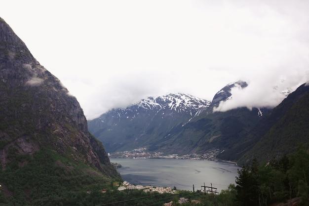Kijk vanaf de top en zware wolken hangen over de fjorden