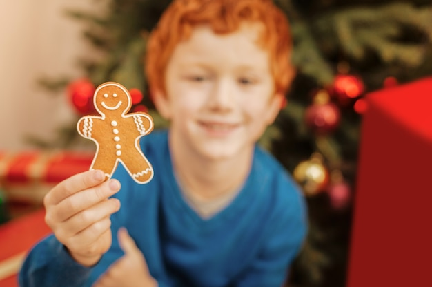 Kijk wat ik heb. selectieve aandacht voor een smakelijke zelfgebakken peperkoekman die wordt vastgehouden door een glimlachend gemberkind dat naast een kerstboom zit.
