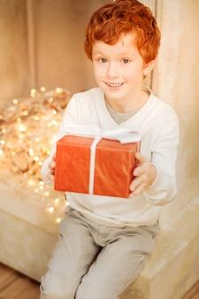 Kijk wat ik heb. selectieve focus op een gezicht van een buitengewoon gelukkige gemberjongen die zijn kerstcadeau demonstreert.