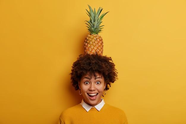 Kijk wat ik kan doen! vrolijke grappige vrouw met afro kapsel houdt sappige ananas op het hoofd, heeft plezier en lacht