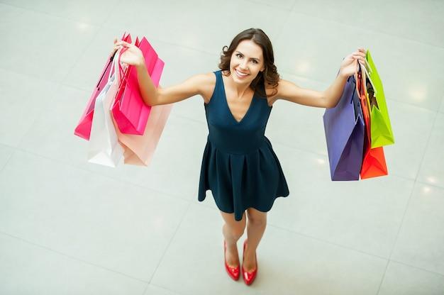 Kijk wat ik krijg! bovenaanzicht van mooie jonge vrouw die boodschappentassen vasthoudt en naar de camera glimlacht