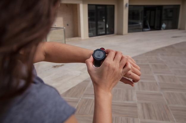 Kijken naar de smartwatch op de loopband running in the gym-concept active lifestyle-cocept