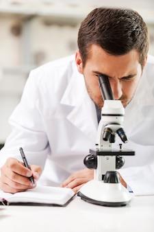 Kijken naar de toekomst van de wetenschap. ernstige jonge wetenschapper in wit uniform met behulp van microscoop en schrijven in notitieblok terwijl hij op zijn werkplek zit