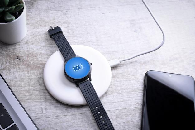 Kijken naar draadloos opladen met oplaadindicator op het scherm. op de desktop, vlakbij de laptop. bovenaanzicht. plaats voor tekst