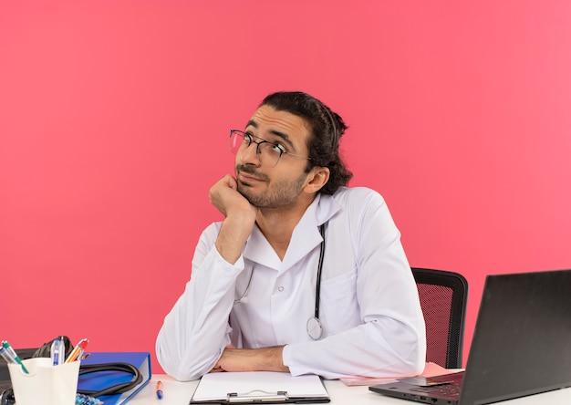 Kijken naar een tevreden jonge mannelijke arts met een medische bril die een medisch gewaad draagt met een stethoscoop die aan het bureau zit