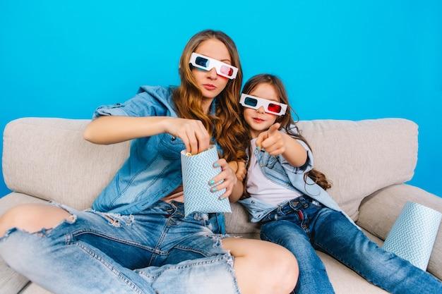 Kijken naar film in 3d-bril van gelukkige moeder en haar dochter in jeanskleren op bank geïsoleerd op blauwe achtergrond. gelukkige familie tijd samen, popcorn eten, positiviteit uitdrukken