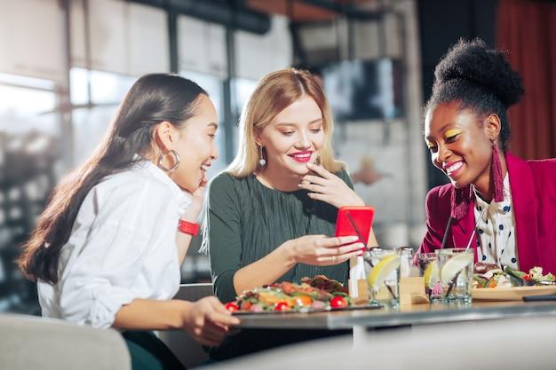 Kijken naar grappige video drie zakenvrouwen kijken naar grappige video op rode smartphone die in restaurant zit
