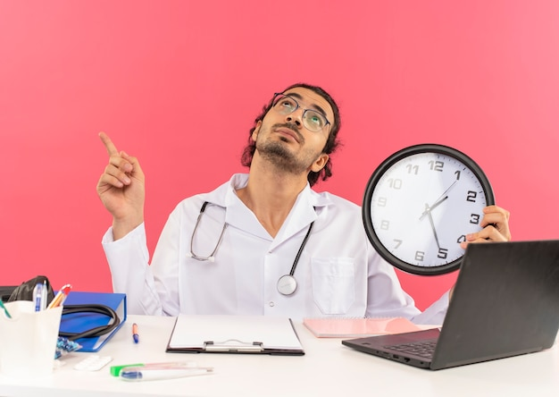 Kijken naar jonge mannelijke arts met een medische bril die een medisch gewaad draagt met een stethoscoop die aan het bureau zit