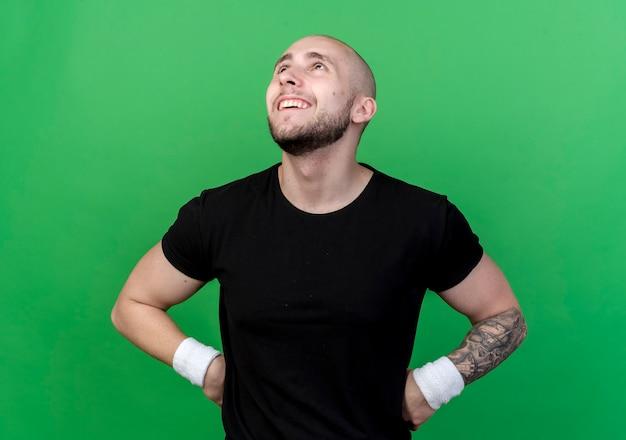 Kijken naar lachende jonge sportieve man met polsbandje handen op heup zetten op groene achtergrond
