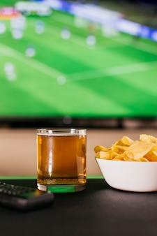 Kijken naar voetbal concept met bier en chips