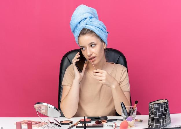Kijkend aan de kant zit een mooi meisje aan tafel met make-uptools gewikkeld haar in een handdoek die lipgloss toepast, spreekt op telefoon geïsoleerd op roze muur