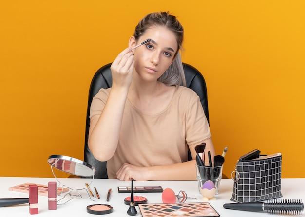 Kijkend camera jong mooi meisje zit aan tafel met make-up tools oogschaduw toe te passen met make-up borstel geïsoleerd op oranje muur
