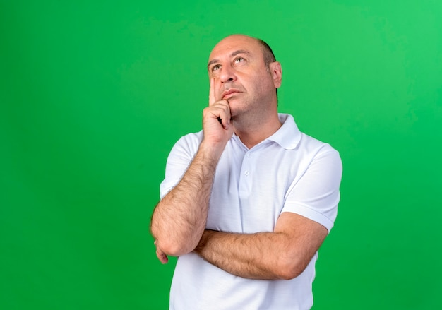Kijkend denken casual volwassen man hand op wang zetten geïsoleerd op groene muur