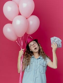 Kijkend denken jong meisje met bril en roze hoed met ballonnen en contant geld geïsoleerd op roze achtergrond