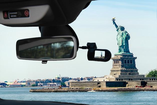 Kijkend door een dashcam-autocamera op een voorruit met uitzicht op het vrijheidsbeeld, iconisch monument op liberty island in de haven van new york, vs.