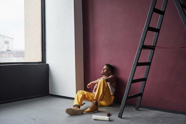Kijkend door het raam. jonge afro-amerikaanse werknemer in het gele uniform heeft een baan