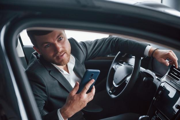 Kijkend door het raam. moderne zakenman probeert zijn nieuwe auto in de auto salon